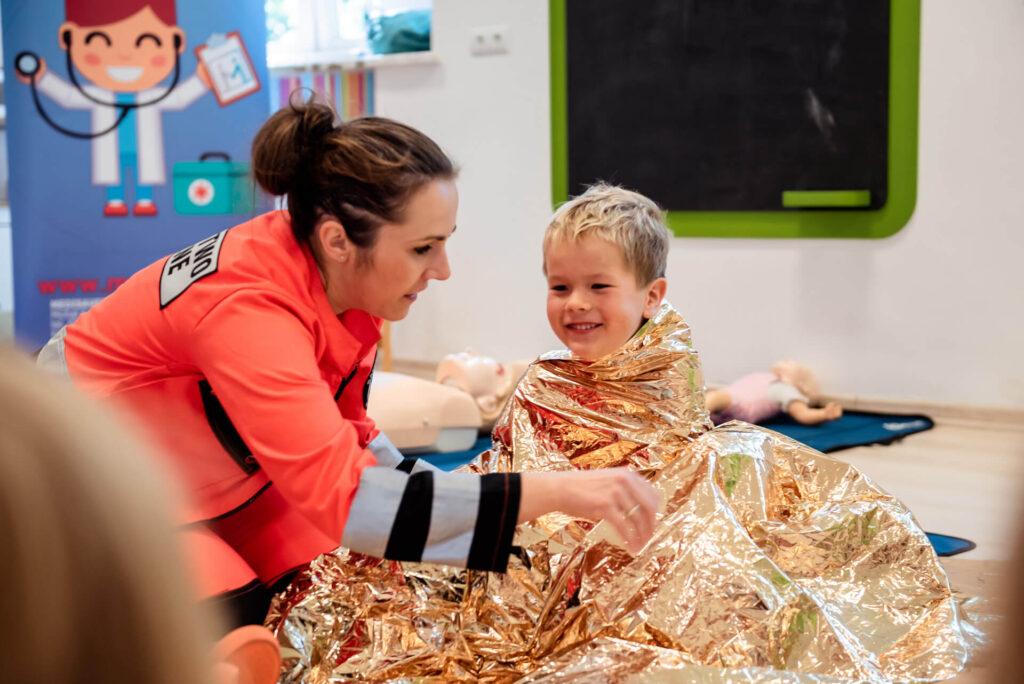 Chłopczyk okryty kocem - Zajęcia z pierwszej pomocy w Przedszkolu na Wiejskiej w Milanówku